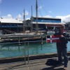 PC Tony Spencer holds the burgee in Auckland, NZ with classic yacht Waitangi in the background